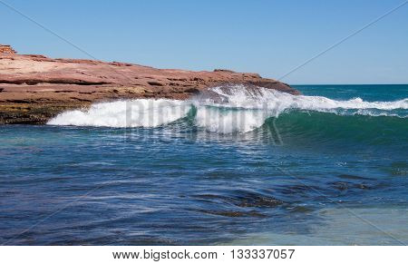 Indian Ocean waves rolling into the inlet with natural sandstone rock formation at Pot Alley on a clear day in Kalbarri, Western Australia.