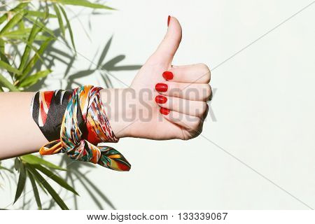 Female hand showing like sign with thumb up