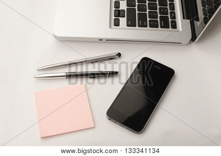 Working in office situation with notebook and smartphone