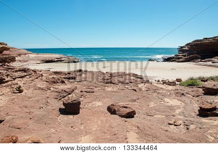 Secluded cove at the Pot Alley gorge with red sandstone formations and turquoise Indian Ocean waters under a clear blue sky in Kalbarri, Western Australia.