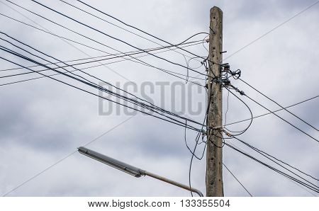 electric pole power lines and wires with dark clouds.