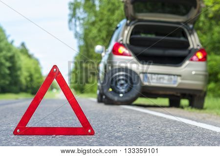 Red warning sign and broken car on the roadside. Focus on red triangle.