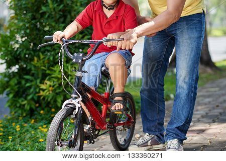 Father helping his son riding bicycle for the first time