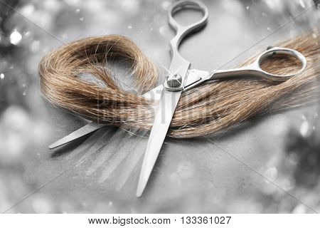 Hairdresser's scissors with strand of brown hair on grey background