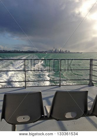 On a ferry on the Waitemata Harbour (Auckland Harbour) on a moody grey day, with the Auckland CBD skyline in the distance.