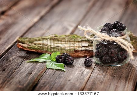 Fresh Blackberry in a glass jar on wooden table close up with