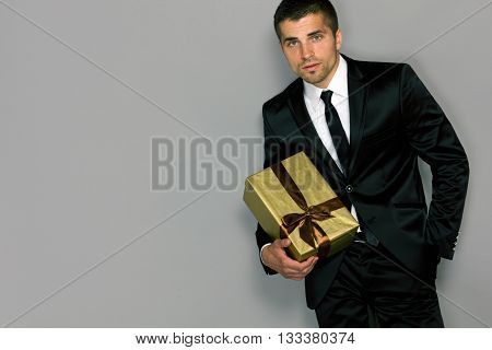 man with a gift box in a suit