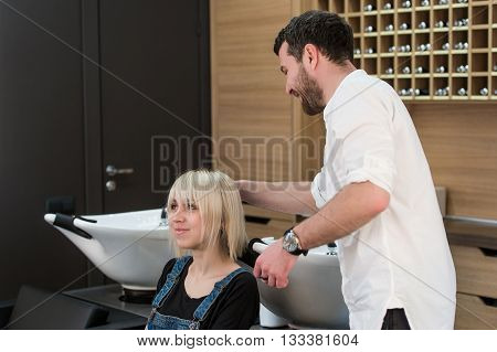 Cheerful dark-haired man doing hairstyle for teen blonde girl in hairdressing saloon.