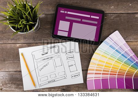 website wireframe sketch and digital tablet on wooden table