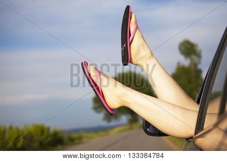 Woman's legs out of car windows.Freedom, travel and vacation road trip concept lifestyle image.