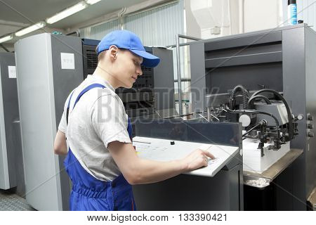 Young man in cap working on offset printing machine in print factory