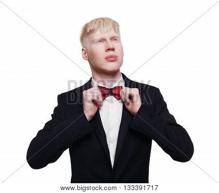 Albino young man portrait. Blond albino guy in suit with red bow tie isolated at white background. Albinism, white, pale skin. Stylish young man, boy in suit.