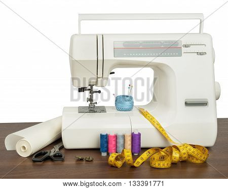 Sewing machine and sewing accessories on wooden table. White background. Front view. Industry template for design