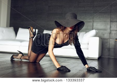 Sexy woman in black hat posing on the floor in luxury flat sensuality