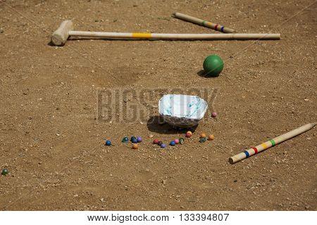 Marble balls on sand background. Croquet mallet on sand background. Playing equipment for children. Sport for children.