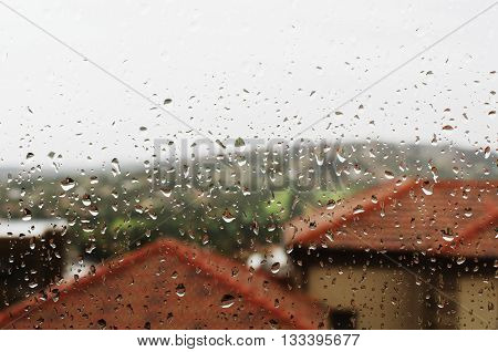 glass with rain drops on a background of houses with red roofs, selective focus, background