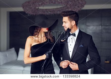 Sensual milf woman in black hat and whip holding young macho lovers chin poster