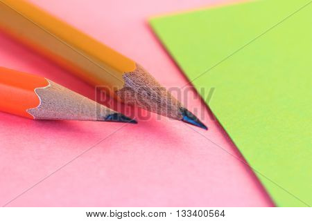 Pencil And A Paper Note Up Close. Simple Pencil And Paper Note. Closeup Pink And Green Paper Note Wi