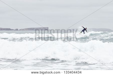 Young male surfer wearing blue wetsuit riding on wave during summer morning surfing session - water sports concept. Baleal, Peniche, Portugal