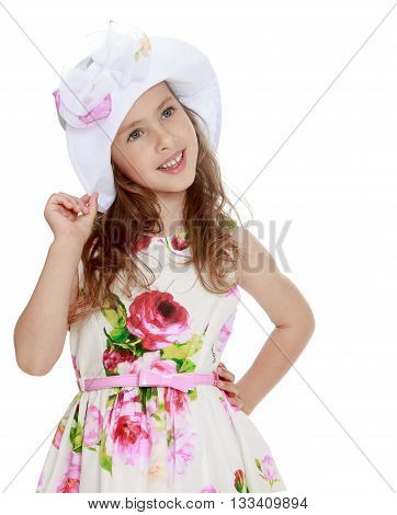 Cute little girl in fine white dress with roses hand adjusts his Panama on his head. Close-up - Isolated on white background