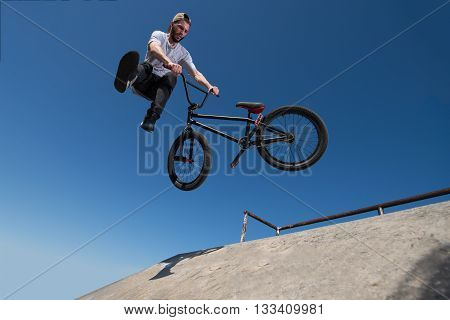 Bmx rider performing a tail whip at a quarter pipe ramp on a skatepark.