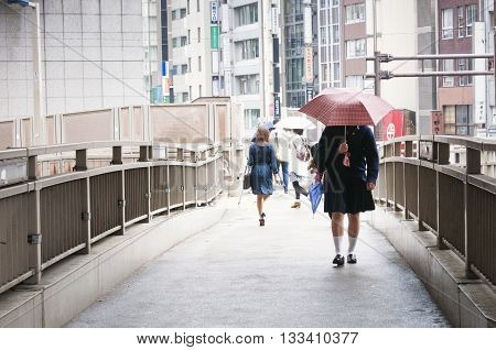 TOKYO - APRIL 23 2011: schoolgirl crossing pedestrian bridge under red umbrella in Shibya district on April 23 2011 in Tokyo Japan.