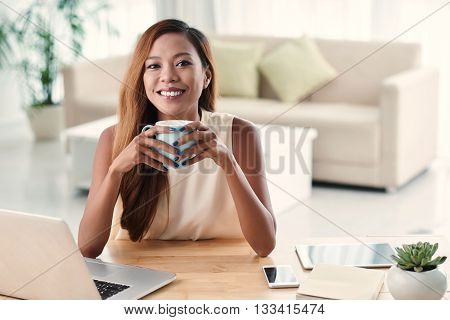 Portrait of beautiful Filipino girl holding cup of hot chocolate