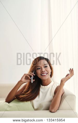 Pretty Filipino woman talking on the phone at home