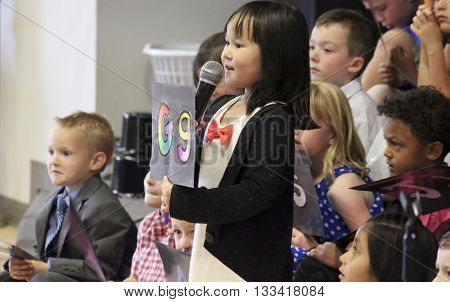 SUMMERLIN, NEVADA, MAY 26. Ethel W. Staton Elementary School on May 26, 2016, in Summerlin, Nevada. A little girl with a microphone holds up the letter G at a kindergarten graduation at Ethel W. Staton Elementary School in Summerlin Nevada.