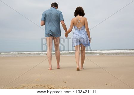 Romantic Middle Aged Loving Couple Walking On The Beach.