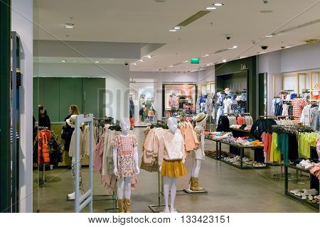 Moscow, Russia - March 29, 2016: People and plastic mannequins in clothes store of the shopping and entertainment center