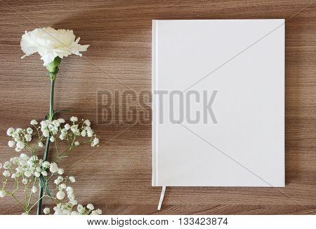 Blank white book journal wedding guestbook notebook mockup. Object for design and branding. White flowers and wooden texture top view.