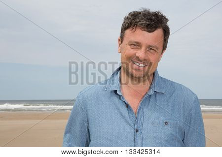 Portrait Of Middle Aged Man Standing At The Beach Smiling