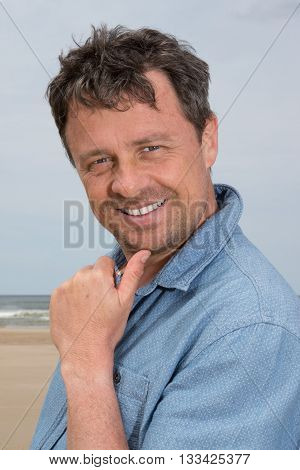 Thinking Middle Aged Man Standing At The Beach Smiling