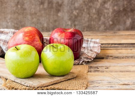 Close up of a red apple and green apple on a wooden table. Fresh red apple on old wooden table background. red and green apple on wood table