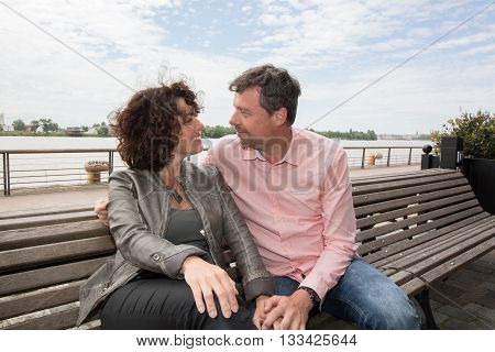 Cheerful Middle-aged Couple Embracing Outside On The Bench