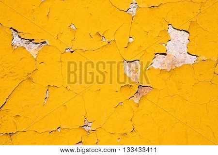 Textured abstract background of yellow paint on exterior wall that is cracked and chipping