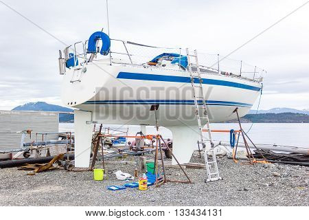 A white boat being repaired and restored in the port