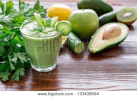 Left glass of green vegetable smoothie near ingredients celery avocado cucumber apple kiwi and herbs right empty space on wooden background. Green vegetable smoothie and ingredients. Horizontal.