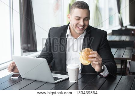 Portrait Of Young Cheerful Businessman Eating Hamburger While Working In Cafe