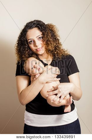 Brunette Mom with her newborn baby isloated on off white background