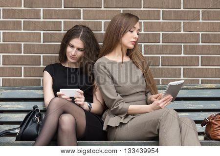 Two Young Women Sitting On Bench Using Their Own Devices