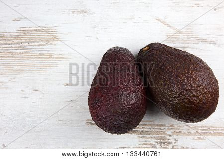 Two dark avocado fruit on white old wooden blacie.Horizontal flat top view
