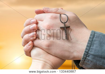 Priest Is Blessing Woman At Sun Set. Clasped Hands Holding Cross