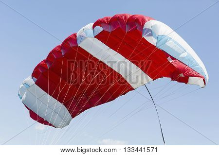 Red parachute on a blue sky. Concept sport poster