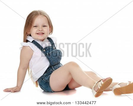 Laughing little girl with long blond hair in denim overalls sitting on the floor - Isolated on white background