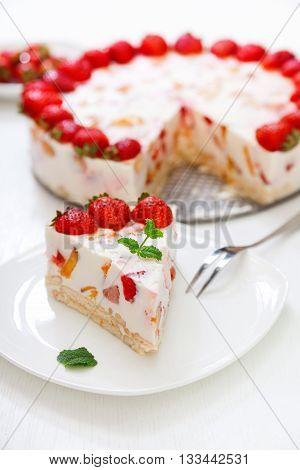 Cake with strawberries gelly yogurt and cherries. Surface view. Isolated on white background. One piece in a white plate. Vertical shot