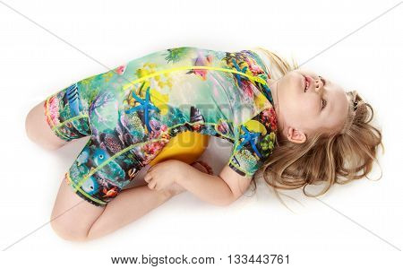 Little girl in swimsuit lying bent on the ball - Isolated on white background