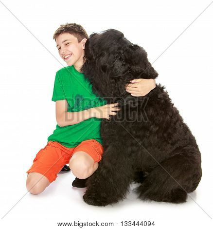 School-age boy hugging a large, shaggy black dog-Isolated on white background