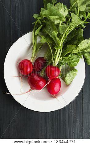 Fresh Radish In White Plate On A Dark Wooden Background